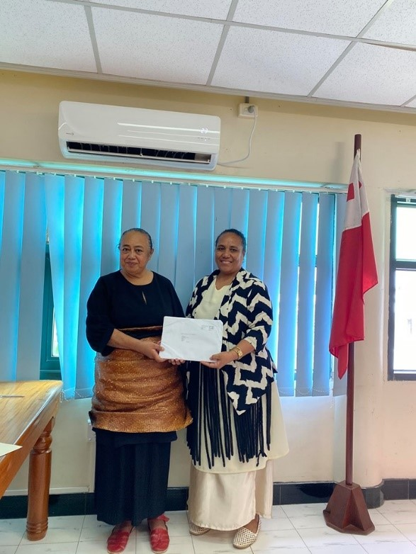 Mrs. Mele Kafo'atu Mafile'o receiving her scholarship package award from Madam CEO of Justice, Mrs. Temaleti. M. A. Pahulu