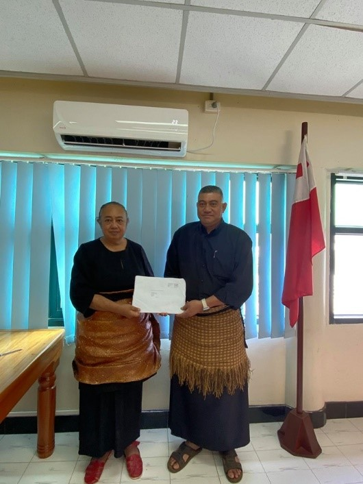 Mr. Viliami Pone Fotu receiving his scholarship package award from Madam CEO of Justice, Mrs. Temaleti. M. A. Pahulu